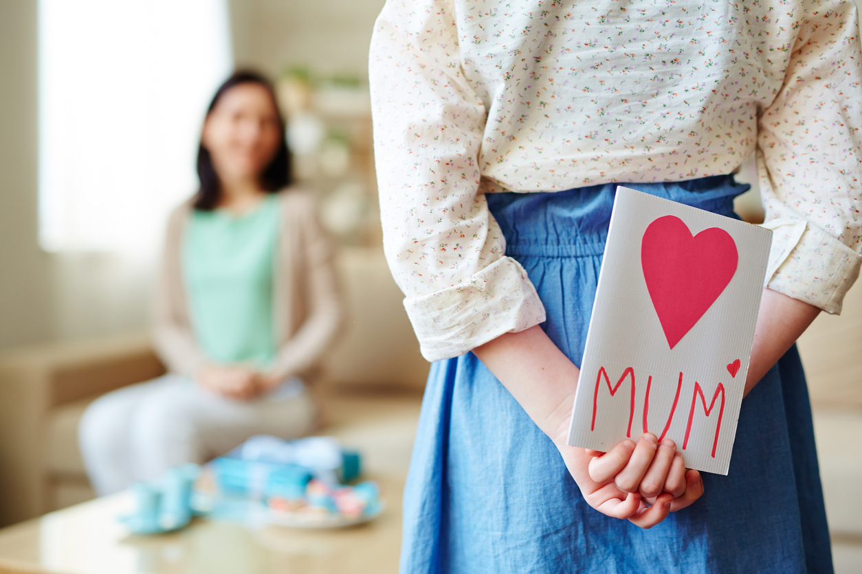 Girl hiding greeting card for mother behind back