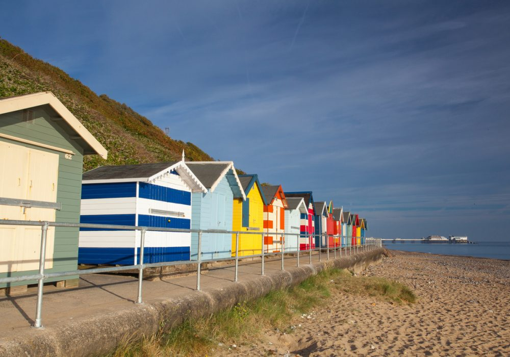 Beach huts along side Cromer beach on a sunny day.