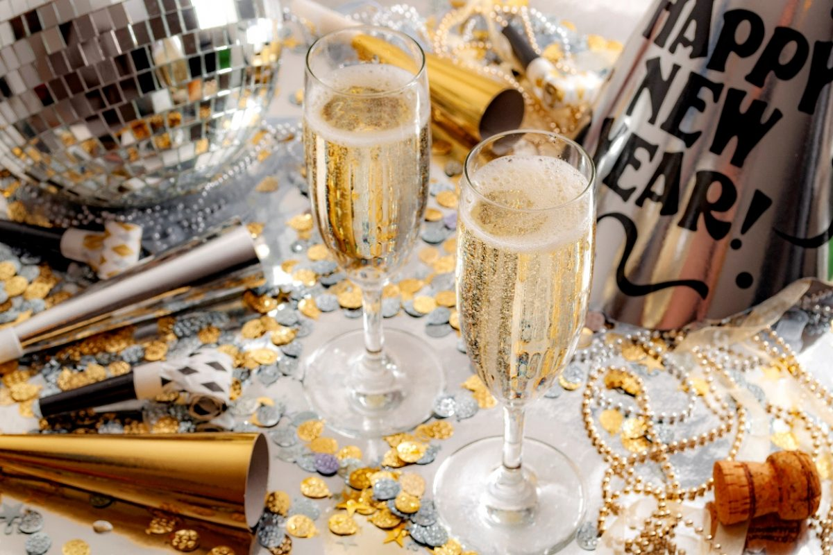 Happy new year celebration concept theme with close up on two glasses of champagne, disco ball covered in mirror, noise makers and party trumpets, confetti, beads and a cork on silver background (Happy new year celebration concept theme with close up